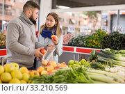 Купить «Friendly couple examining apples in grocery shop», фото № 33210569, снято 20 ноября 2019 г. (c) Яков Филимонов / Фотобанк Лори