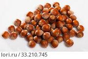 Unpeeled hazelnut on white surface closeup. Стоковое фото, фотограф Яков Филимонов / Фотобанк Лори