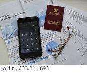 Счета за коммунальные услуги,калькулятор и пенсионное удостоверение. Редакционное фото, фотограф александр лупкин / Фотобанк Лори