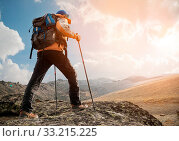 Купить «A lonely tourist with a backpack and wearing sunglasses enjoys the views high in the mountains of the Caucasus where there is no grass, the village and snow at sunset. View from the back», фото № 33215225, снято 7 июля 2020 г. (c) easy Fotostock / Фотобанк Лори