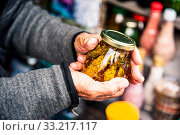 Old wrinkled hands hold a jar with mountain jam from the leaves of Caucasian trees leaves in the mountains. Стоковое фото, фотограф Zoonar.com/Ian Iankovskii / easy Fotostock / Фотобанк Лори