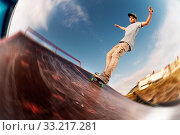 Купить «Teen skater hang up over a ramp on a skateboard in a skate park. Wide angle», фото № 33217281, снято 7 июля 2020 г. (c) easy Fotostock / Фотобанк Лори