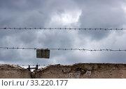Купить «Gloomy barbed wire on dark fence and grey sky.», фото № 33220177, снято 1 апреля 2020 г. (c) easy Fotostock / Фотобанк Лори