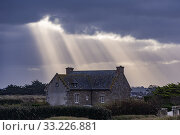 France, Finistere, Pagan Country, Coast of Legends, Meneham, house under the rays of the diffuse sun passing through clouds. Стоковое фото, фотограф Morales / age Fotostock / Фотобанк Лори