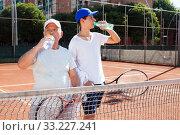 Купить «tennis players of different generations drink water on tennis court», фото № 33227241, снято 29 июля 2019 г. (c) Татьяна Яцевич / Фотобанк Лори