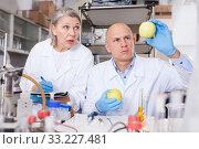 Купить «Scientists taking notes while performing experiments», фото № 33227481, снято 24 января 2019 г. (c) Яков Филимонов / Фотобанк Лори