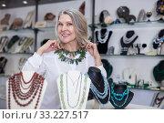 Купить «Woman trying on a aventurine necklace and earrings at a jewelry store», фото № 33227517, снято 2 мая 2019 г. (c) Яков Филимонов / Фотобанк Лори