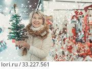 Купить «Woman is preparing for Christmas and choosing decorative X-mas tree», фото № 33227561, снято 21 декабря 2017 г. (c) Яков Филимонов / Фотобанк Лори