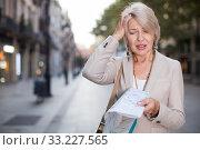 Купить «Adult woman 50-60 years old is walking with map in classic dress», фото № 33227565, снято 3 сентября 2017 г. (c) Яков Филимонов / Фотобанк Лори