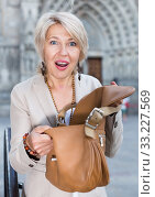 Mature woman is upset because her purse was been stole from bag. Стоковое фото, фотограф Яков Филимонов / Фотобанк Лори