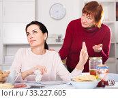 Upset woman quarrel with mother at table. Стоковое фото, фотограф Яков Филимонов / Фотобанк Лори