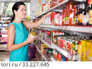 Купить «Portrait of pretty female in the shop holding tomato paste», фото № 33227645, снято 6 июня 2017 г. (c) Яков Филимонов / Фотобанк Лори
