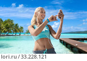 Купить «happy woman with smartphone and earphones on beach», фото № 33228121, снято 5 июля 2015 г. (c) Syda Productions / Фотобанк Лори