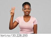 Купить «happy african american woman showing three fingers», фото № 33228293, снято 26 января 2020 г. (c) Syda Productions / Фотобанк Лори