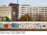 Купить «Construction of residential and office buildings at the East-Side-Gallery in Muehlenstrasse in Berlin-Friedrichshain», фото № 33228797, снято 10 ноября 2018 г. (c) Caro Photoagency / Фотобанк Лори