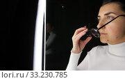 Купить «woman in glasses over white illumination on black», видеоролик № 33230785, снято 23 декабря 2019 г. (c) Syda Productions / Фотобанк Лори