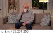Купить «happy senior man drinking tea at home in evening», видеоролик № 33231253, снято 4 января 2020 г. (c) Syda Productions / Фотобанк Лори
