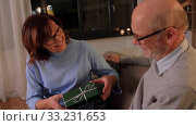 Купить «happy senior couple with gift box at home», видеоролик № 33231653, снято 20 января 2020 г. (c) Syda Productions / Фотобанк Лори