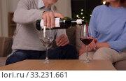 Купить «happy senior couple drinking red wine at home», видеоролик № 33231661, снято 20 января 2020 г. (c) Syda Productions / Фотобанк Лори