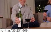 Купить «happy senior couple drinking red wine at home», видеоролик № 33231669, снято 20 января 2020 г. (c) Syda Productions / Фотобанк Лори
