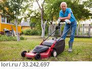 Купить «Positive elderly man with lawnmower when mowing the lawn», фото № 33242697, снято 30 мая 2020 г. (c) Яков Филимонов / Фотобанк Лори