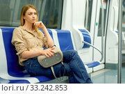 Купить «Smiling young woman passenger standing inside train at metro», фото № 33242853, снято 31 марта 2019 г. (c) Яков Филимонов / Фотобанк Лори