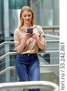 Купить «Young positive smiling woman reading from mobile phone screen in metro», фото № 33242861, снято 31 марта 2019 г. (c) Яков Филимонов / Фотобанк Лори