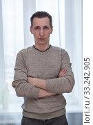 Young man with crossed arms looking at camera. Стоковое фото, фотограф Кекяляйнен Андрей / Фотобанк Лори