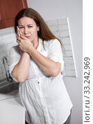 Unhappy woman with toothache standing in domestic kitchen, holding her cheek with hands. Стоковое фото, фотограф Кекяляйнен Андрей / Фотобанк Лори