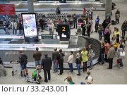 Passengers wait their bags near baggage conveyor belt. Baggage claim is in Pulkovo International airport. It is modern terminal for arriving people in city (2015 год). Редакционное фото, фотограф Кекяляйнен Андрей / Фотобанк Лори
