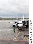 Aircraft of Ural Airlines is connected with passenger boarding bridge to airport terminal. The Koltsovo International Airport. Екатеринбург (2015 год). Редакционное фото, фотограф Кекяляйнен Андрей / Фотобанк Лори