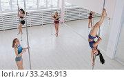 Young women dancing on the poles in bright white studio with big mirrors. Стоковое фото, фотограф Константин Шишкин / Фотобанк Лори