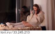 Купить «woman with coffee or tea cup on windowsill at home», видеоролик № 33245213, снято 21 января 2020 г. (c) Syda Productions / Фотобанк Лори