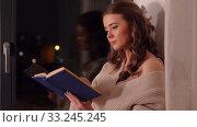 Купить «woman reading book sitting on windowsill at home», видеоролик № 33245245, снято 21 января 2020 г. (c) Syda Productions / Фотобанк Лори
