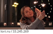 Купить «happy young woman with sparklers at home», видеоролик № 33245269, снято 21 января 2020 г. (c) Syda Productions / Фотобанк Лори