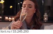 Купить «young woman drinking champagne at home at night», видеоролик № 33245293, снято 17 февраля 2020 г. (c) Syda Productions / Фотобанк Лори