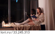woman reading book sitting on windowsill at home. Стоковое видео, видеограф Syda Productions / Фотобанк Лори