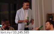 Купить «happy male friends drinking beer at home at night», видеоролик № 33245585, снято 12 января 2020 г. (c) Syda Productions / Фотобанк Лори