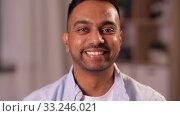 Купить «portrait of happy smiling indian man at home», видеоролик № 33246021, снято 13 января 2020 г. (c) Syda Productions / Фотобанк Лори