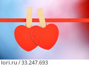Two red hearts at ribbon on multicolor background. Стоковое фото, фотограф Anton Eine / PantherMedia / Фотобанк Лори