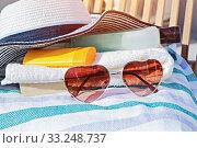 Купить «Sunscreen cream cosmetic bottles, sunglasses and summer hat on deck chair», фото № 33248737, снято 2 мая 2017 г. (c) Kira_Yan / Фотобанк Лори