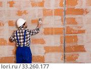 Купить «Workman is plastering the wall at the place», фото № 33260177, снято 6 марта 2019 г. (c) Яков Филимонов / Фотобанк Лори