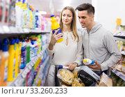 Купить «Smiling couple choosing household detergents», фото № 33260233, снято 7 ноября 2019 г. (c) Яков Филимонов / Фотобанк Лори