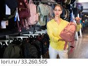 Купить «Portrait of young female shopper looking for backpack in store», фото № 33260505, снято 7 октября 2019 г. (c) Яков Филимонов / Фотобанк Лори
