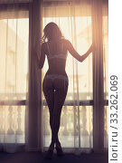 Sexy slim dark silhouette of a young woman against the background of a window with curtains and sun rays. Стоковое фото, фотограф katalinks / Фотобанк Лори