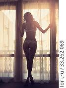 Купить «Sexy slim dark silhouette of a young woman against the background of a window with curtains and sun rays», фото № 33262069, снято 20 июля 2016 г. (c) katalinks / Фотобанк Лори