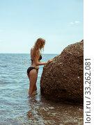 Beautiful slim young woman in a black bikini swimsuit resting on a rocky beach. Стоковое фото, фотограф katalinks / Фотобанк Лори
