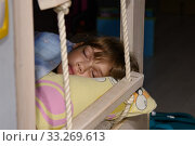 The girl fell asleep on the edge of the bed, next to the rope ladder on the second tier. Стоковое фото, фотограф Иванов Алексей / Фотобанк Лори