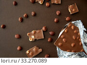 Купить «milk chocolate bar with hazelnuts in foil wrapper», фото № 33270089, снято 1 февраля 2019 г. (c) Syda Productions / Фотобанк Лори