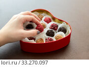 hand with candies in heart shaped chocolate box. Стоковое фото, фотограф Syda Productions / Фотобанк Лори